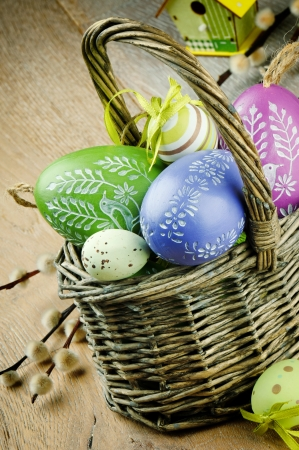 Basket with colorful Easter eggs on wooden table photo
