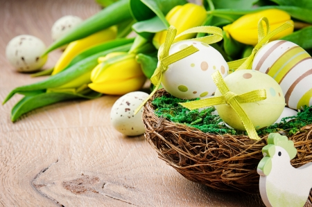 Easter eggs in holiday setting with yellow tulips photo