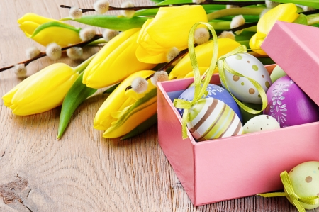 Colorful Easter eggs in open gift box with tulips photo
