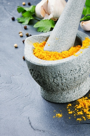 Mortar and pestle with curry powder and pepper photo