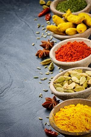 culinair: Kleurrijke mix van kruiden in oude kommen op steen achtergrond Stockfoto