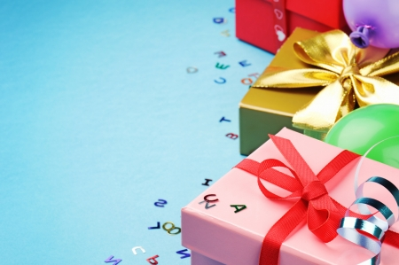 Colorful birthday gift boxes over blue background photo