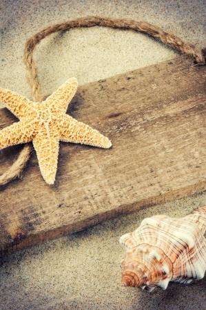 estrella de mar: Vieja tarjeta de madera con copyspace y conchas marinas Foto de archivo