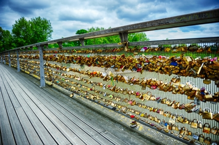 close icon: Love locks on Paris bridge at cloudy summer day Stock Photo