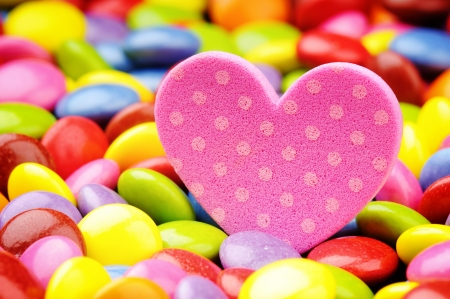 Pink heart and colorful smarties. Love concept photo