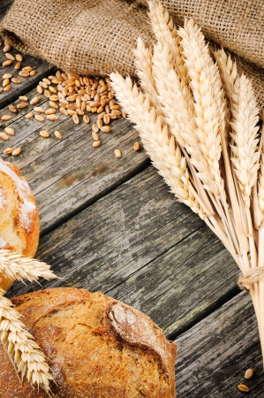 Agricultural frame with bread and wheat on wooden background photo