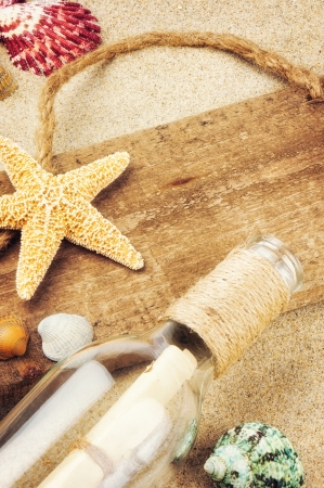 Old wooden board with seashells and bottle on sand photo