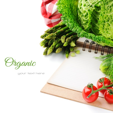 Fresh organic vegetables and cooking book isolated over white photo