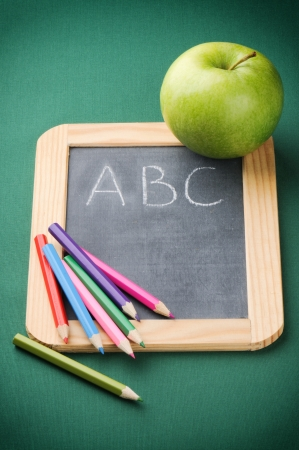 Colorful crayons on blackboard. Back to school concept photo