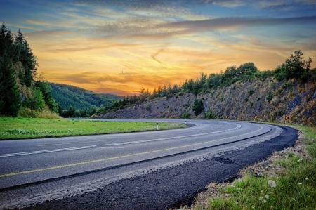 Landschap met bochtige weg in de zomer zonsondergang