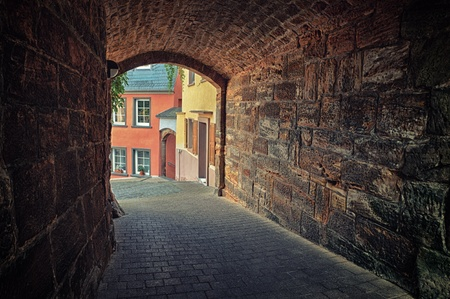 Arched pedestrian tunnel in small European city at summer day