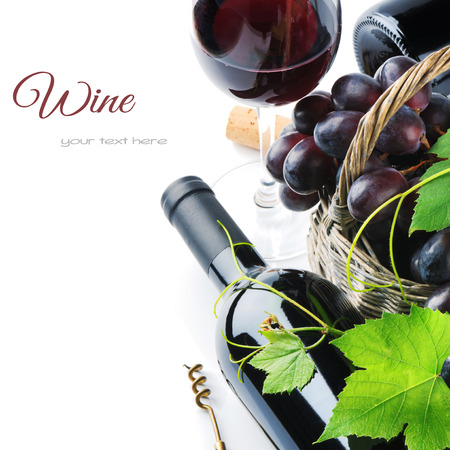 Bottle of red wine with freshly harvested grape in basket