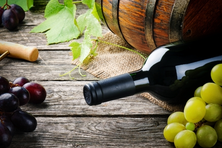 Bottle of red wine and fresh grape on wooden table photo