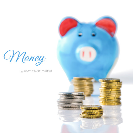 Piggy bank and piles of coins isolated over white photo