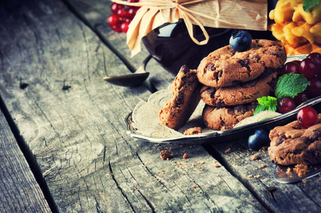 Chocolate chip cookies and jam in vintage setting photo
