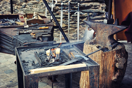 ancient blacksmith: Blacksmiths working process on metal at forge