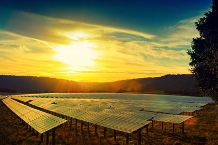 PLACAS SOLARES: Hermosa puesta de sol sobre el campo de la energía solar en el día de verano Foto de archivo