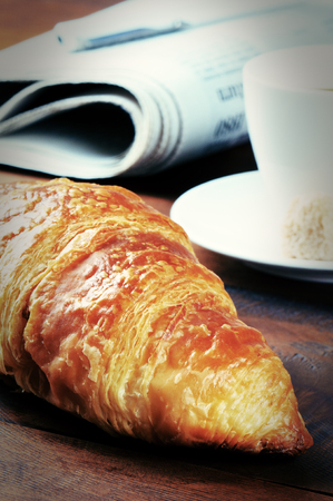 Breakfast with fresh croissant and coffee on wooden table photo