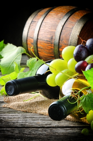Bottles of red and white wine with fresh grape and wooden barrel photo