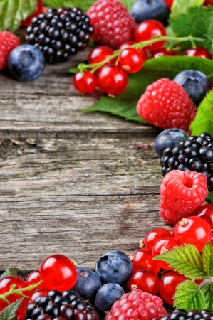 Frame with fresh summer berries on wooden background photo