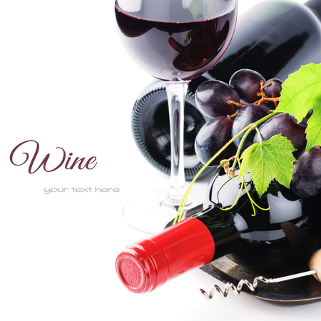 Bottles of red wine with fresh grape isolated over white photo