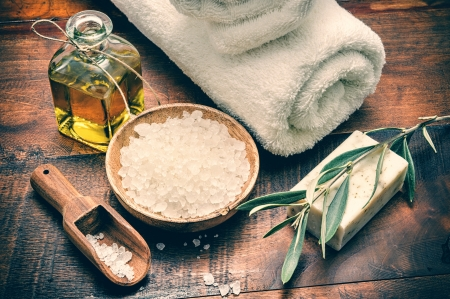 Spa setting with natural olive soap and sea salt on wooden table photo