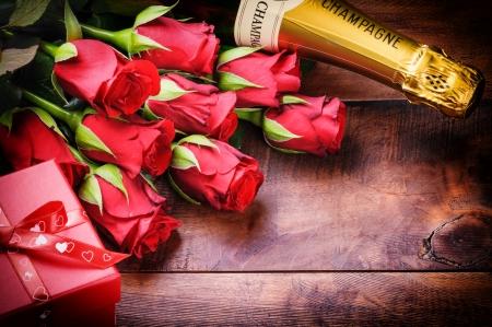 roses rouges: Le r�glage de la Saint-Valentin avec des roses rouges, champagne et un cadeau sur fond de vieux bois Banque d'images