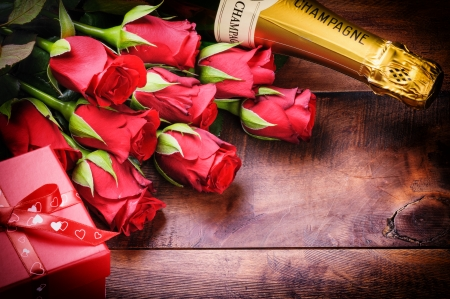 Valentines setting with red roses, champagne and gift on old wood background photo