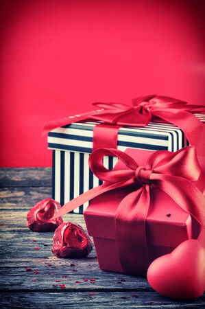 Valentines presents and red chocolate hearts on wooden table photo