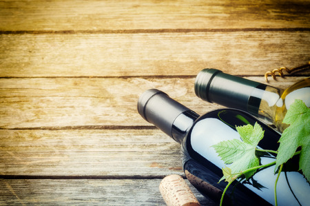 degustation: Bottles of red and white wine on wooden background Stock Photo