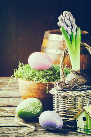 flower basket: Easter setting with hyacinth and decorative eggs on old wooden table
