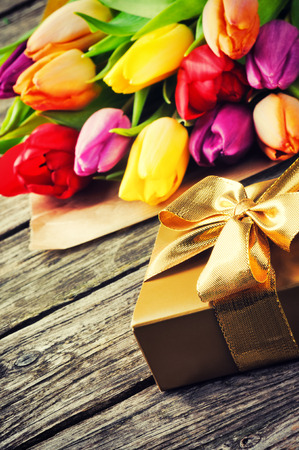 Multicolor tulips bouquet and gift box on wooden table photo