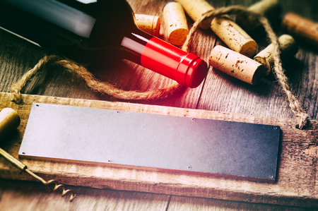 Rustic setting with red wine bottle, corks and wooden board photo