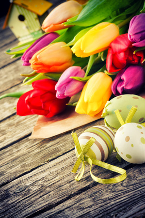Ajuste de Pascua con los tulipanes multicolores y huevos decorativos photo