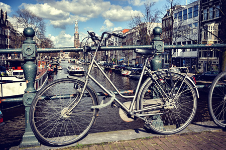 Old bicycle on bridge. Amsterdam cityscape at sunny day