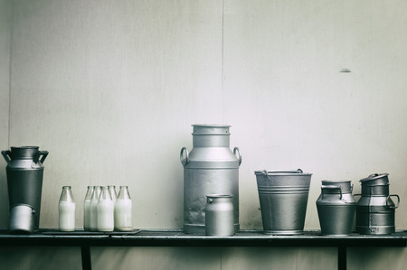 Old milk jugs, cans and bottles at dairy farm photo