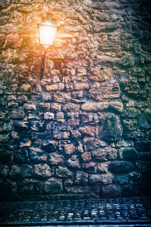 Old stone wall with lantern.Background concept photo
