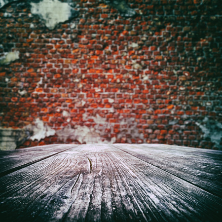 Empty wooden table with old brick wall on the background photo