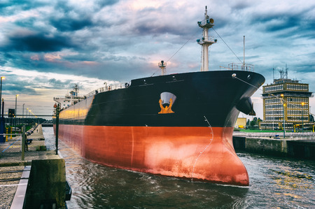 Vrachtschip in de haven bij zonsondergang Stockfoto