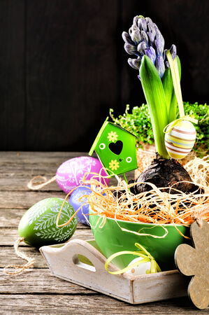 Easter setting with hyacinth and decorative eggs on wooden table photo