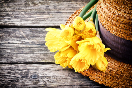 Straw hat with spring daffodils on old wood background photo