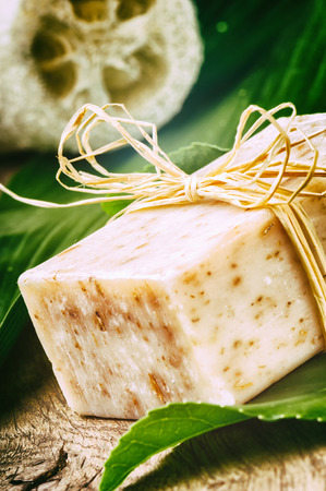 Natural handmade soap bar on green leaf photo
