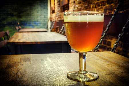 Glass of fresh beer in rustic pub Stock Photo