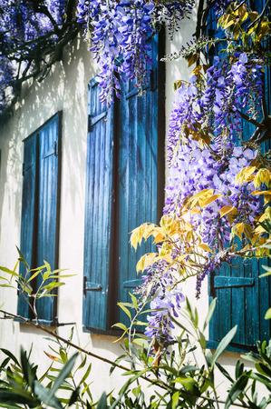 Las viejas ventanas con persianas azules. Casa francesa tradicional
