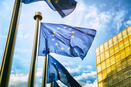 Agitando bandeiras da UE em frente da Comissão Europeia em Bruxelas