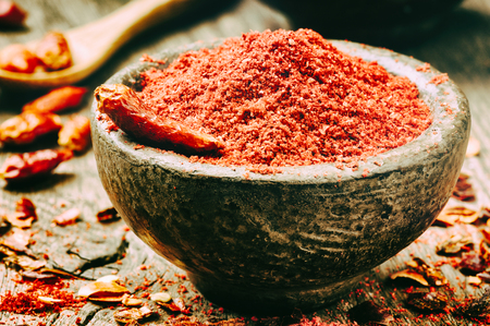 pepper flakes: Ground hot chili pepper in a rustic bowl Stock Photo