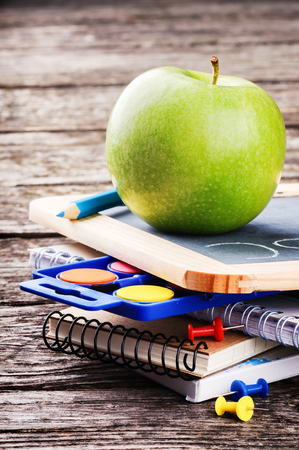 Colorful school supplies and green apple photo