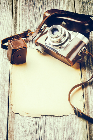 Retro camera on old wood background with vintage paper Stock Photo - 30121225