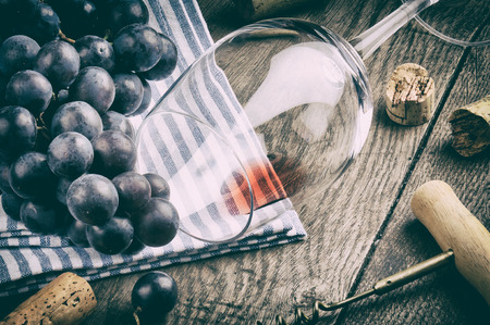 Retro setting with empty wine glass and grapes on wooden table photo