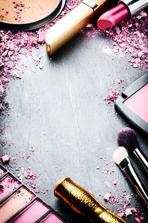 productos de belleza: Marco con varios productos de maquillaje en tono rosa Foto de archivo